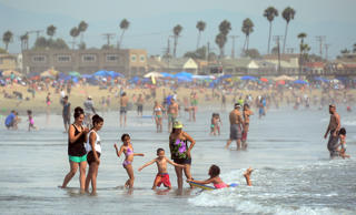 A girl catches a wave on her boogie board for her family to see as crowds took t...