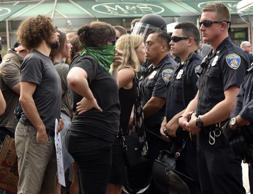 Protesters look through a line of Baltimore City police as Kwame Rose, an activist, is detained by police as protesters rallied outside the Baltimore courthouse during the first court hearing for six Baltimore police officers who are charged in the death of Freddie Gray, a black man who died a week after suffering a critical spine injury in custody.