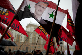 Pro-Kremlin youths hold a Syrian flag bearing a portrait of Syrian President Bashar al-Assad during a picket in protest against American policy in front of the U.S. Embassy in Moscow, Russia, Friday, April 3, 2015.