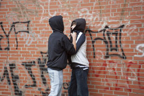 VARIOUS MODEL RELEASED Teenager pushing a smaller boy violently against a wall, posed scene