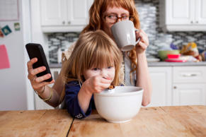 Girl eating breakfast, mother drinking coffee and looking at smartphone.