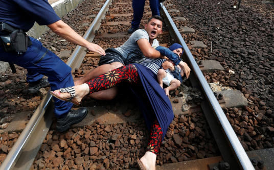 Hungarian policemen stand by the family of migrants as they wanted to run away a...