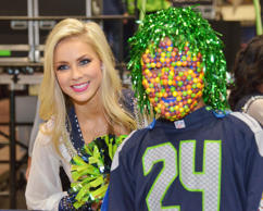 Seattle Seahawks sea gals cheerleader poses with fan Javon Washington wearing the No. 24 jersey of running back Marshawn Lynch (not pictured) and a Skittles mask perform during tailgating festivities before the game against the Oakland Raiders at CenturyLink Field.