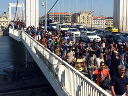 Hundreds of migrants cross the river Danube in Budapest, Friday Sept, 4, 2015, after they decided to walk toward Austria. Thousands have been camped out at Budapest's Keleti train station for days, before they decided to try and reach their destination on foot.