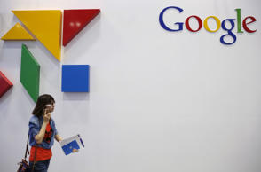 A woman walks past a logo of Google at the Global Mobile Internet Conference (GMIC) 2015 in Beijing, China, April 28, 2015. According to the tech website, The information, Google expects to return to mainland China as early as this fall following a five-year absence.