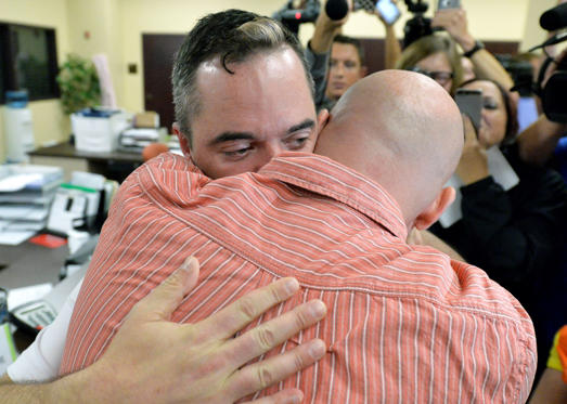 James Yates, left, hugs his partner William Smith Jr., after receiving their marriage license at the Rowan County Judicial Center in Morehead, Ky., Friday, Sept. 4, 2015.  Deputy clerk Brian Mason issued the license, congratulating the couple and shaking their hands as he smiled. Timothy D. Easley/AP