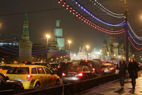 Pedestrians pass queuing traffic near the Kremlin, left, and Red Square, top, in...