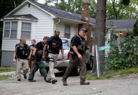 Police officers leave after searching an area for suspects involved in the murde...