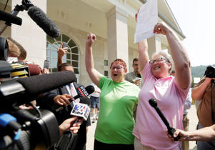 Plaintiffs Karen Roberts, left, and April Miller celebrate after receiving their marriage license from Deputy Clerk Brian Mason at the Rowan County clerk's office in the County Courthouse in Morehead, Ky., on Friday, Sept. 4, 2015.