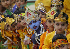 Schoolchildren dressed as Hindu Lord Krishna wait to perform during celebrations...