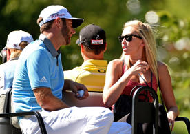 Dustin Johnson rides on a golf cart with his wife Paulina Gretzky during round t...