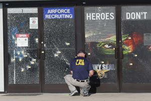 An FBI investigator investigates the scene of a shooting outside a military recruiting center on Friday, July 17, 2015, in Chattanooga, Tenn.