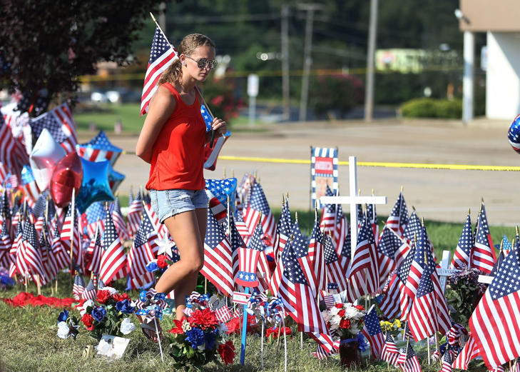 Keari Anderson walks through the memorial near the Armed Forces Career Center/National Guard Recruitment Office which had been shot up on July 19, 2015 in Chattanooga, Tennessee.