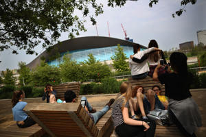 Children relax along the canal at near the aquatics centre in the Olympic Park  in London.