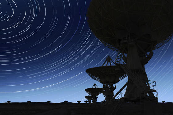 large radio telescopes in silhouette at night with long exposure starry sky (XL)