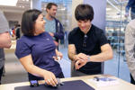 An Apple employee, left, laughs next to a customer trying on Apple's new watch, in San Francisco, Friday, April 10, 2015.