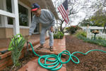 Retired Department of Motor Vehicle customer service representative Raymond Aleman closes his water hose after watering for his new drought resistant garden at his home in the Studio City neighborhood in Los Angeles, Wednesday, May 27, 2015.