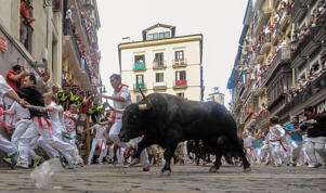 Revellers run with the Tajo and the Reina's fighting bulls entering Estafeta street during the third day of the San Fermin Running of the Bulls festival in Pamplona, Spain.