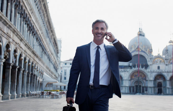 Businessman talking on cell phone and walking through St. Mark's Square in Venice.