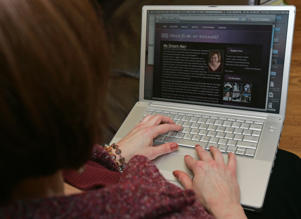A woman uses her laptop to work on her dating website.