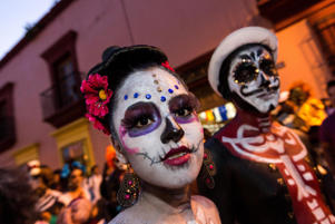A woman dressed as Catrina, the bride of death, at a Comparsa procession during Day of the Dead Festival, Mexico.