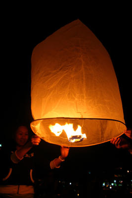 "Locals light a ""kom-loy"" flying lantern on the banks of the Ping River in Chiang Mai. The city is famed for its annual Loi Krathong festival."