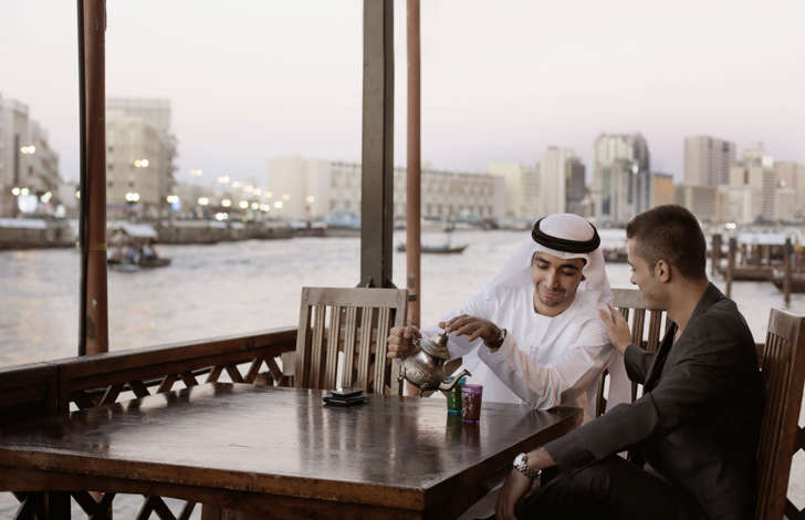 Two men drinking tea in Middle Eastern country.