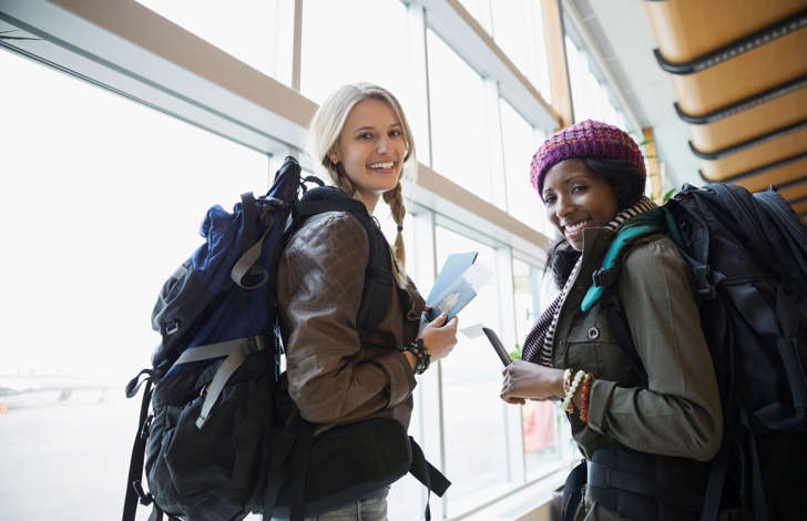 Women with backpacks in airport.