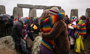 A couple embrace as druids, pagans and revellers gather in the centre of Stonehenge in Wiltshire, England.