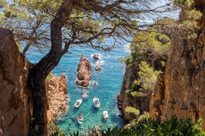 View from above of anchored recreational boats in a hidden cove of the Costa Brava in Catalonia, Spain.