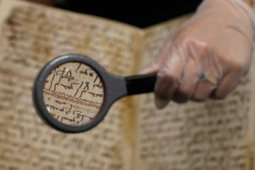 A detail of a fragment of a Koran manuscript is seen through a magnifying glass in the library at the University of Birmingham in Britain July 22, 2015. A British university said on Wednesday that fragments of a Koran manuscript found in its library were from one of the oldest surviving copies of the Islamic text in the world, possibly written by someone who might have known Prophet Mohammad. Radiocarbon dating indicated that the parchment folios held by the University of Birmingham in central England were at least 1,370 years old, which would make them one of the earliest written forms of the Islamic holy book in existence.