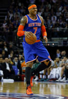 New York Knicks' Carmelo Anthony makes a face as he controls the ball during the Knicks' NBA basketball game against the Milwaukee Bucks at O2 Arena in London, Thursday, Jan. 15, 2015.