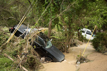 Vehicles came to rest in a creek after deadly flooding in Flat Gap, Ky., Tuesday, July 14, 2015. Flash floods in northern Johnson County outside of Paintsville destroyed homes and vehicles and residents were reported missing a day after the floods.