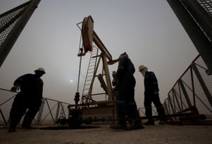 FILE - In this Jan. 8, 2015 file photo, men work on an oil pump during a sandstorm in the desert oil fields of Sakhir, Bahrain. The price of oil dipped below $45 a barrel Tuesday, Jan. 13, 2015, following the latest sign from OPEC that the group doesn't plan to cut production. (AP Photo/Hasan Jamali, File)