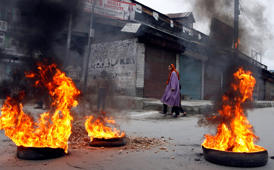 File: A Kashmiri woman walks near burning tyres during a gathering in Srinagar June 5, 2010.