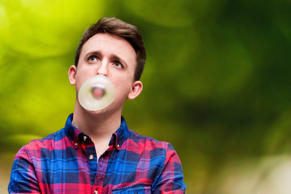 Young man blowing a bubble