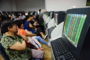 Investors sit in front of computer screens showing stock information at a brokerage house in Qingdao, Shandong province, July 27, 2015.