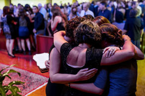 "Members of the Figs, Jillian Johnson's band, embrace each other in solidarity following Johnson's funeral service at Delhomme Funeral Home in Lafayette, La., Monday, July 27, 2015. Jillian Johnson, 33, and Mayci Breaux, 21, were shot and killed last Thursday while watching the movie ""Trainwreck"" at The Grand 16 movie theater in Lafayette, leaving stunned friends and family questioning how two lives off to such promising starts could end so tragically."