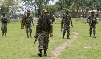 File: Security personnel patrol outside a polling station in Alamganj village, about 280 km (174 miles) west of Guwahati, the main city of India's northeastern state of Assam, April 23, 2009.