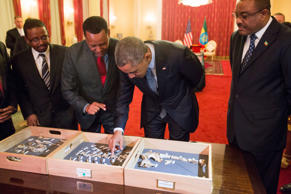 "Ethiopian Prime Minister Hailemariam Desalegn watches at right as President Barack Obama touches ""Lucy,"" part of several hundred pieces of bone representing 40 percent of a female Australopithecus afarensis who was estimated to have lived 3.2 million years ago in Ethiopia, Monday, July 27, 2015, at the National Palace in Addis Ababa."