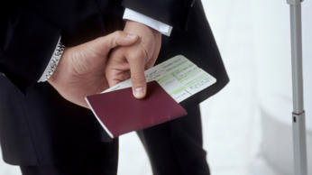 Man holding passport and boarding pass.