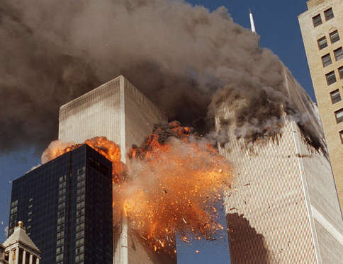 FILE- In this Sept. 11, 2001 file photo, smoke billows from World Trade Center Tower 1 and flames explode from Tower 2 as it is struck by American Airlines Flight 175, in New York. For New Yorkers in or near the World Trade Center on Sept. 11, 2001, the sights and sounds of everyday life can still trigger painful memories and strong psychological reactions to the attacks. (AP Photo/Chao Soi Cheong, File) MANDATORY CREDIT