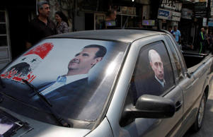 Election poster of Syria's President Bashar al-Assad and a photo of Russian President Vladimir Putin (R) are seen on a car at al-Qardahah town near Latakia city May 26, 2014.