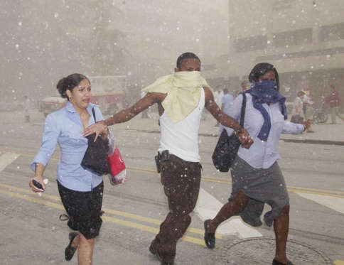 FILE - In this Sept. 11, 2001 file photo, three people make their way through a cloud of caustic dust after terrorists flew two airliners into the World Trade Center towers in New York. For New Yorkers in or near the World Trade Center on Sept. 11, 2001, the sights and sounds of everyday life can still trigger painful memories and strong psychological reactions. (AP Photo/Suzanne Plunkett, File)