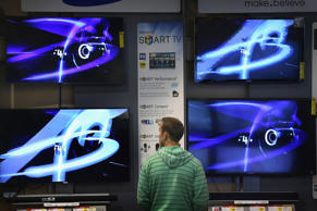 A customer looks over televisions offered for sale at a Best Buy store in Chicago, Illinois.