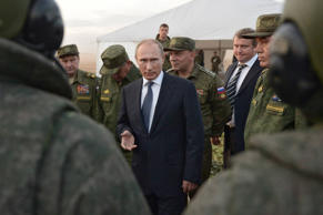 Russian President Vladimir Putin, center, meets with officers after military exercises at Donguz range in Orenburg region, about 1300 kilometers (800 miles) southeast of Moscow, Russia, Saturday, Sept. 19, 2015. Russian President Vladimir Putin on Saturday signaled his intentions to establish a Russian military air base in neighboring Belarus.