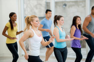 A group of young adults taking a Zumba dance class.