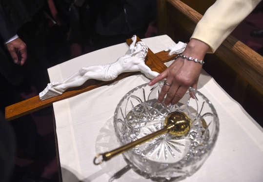 A lady dips her finger in the holy water bowl that Pope Francis used to bless the crowd as he entered the Midday Prayer of the Divine with more than 300 U.S. Bishops at the Cathedral of St. Matthew the Apostle in Washington, Wednesday, Sept. 23, 2015. (Jonathan Newton / The Washington Post via AP)