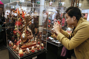 A woman takes pictures of chocolate creations inspired by Salvador Dali as part of a contest at the Paris Chocolate fair (Salon du Chocolat) on October 29, 2014.