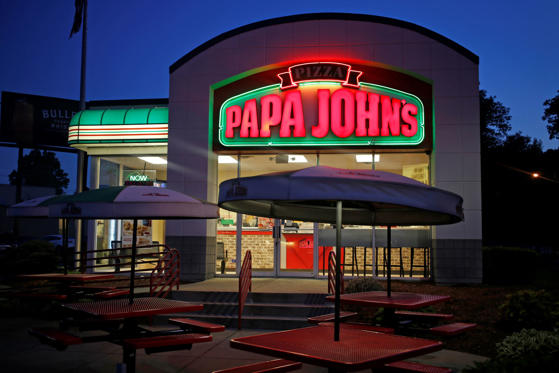 Slide 1 of 11: Neon signage glows at dusk outside a Papa John's International Inc. restaurant in Louisville, Ky.